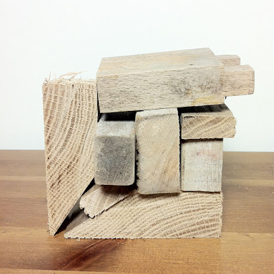 Wood off-cuts stacked together to form almost a square shape.