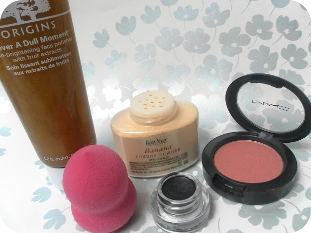 A picture of Ben Nye Banana Powder, Origins Never A Dull Moment face polisher, a beauty blender, MAC blush in springsheen and Bobbi Brown gel liner