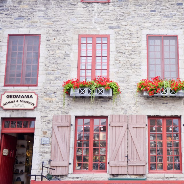 Red trim, old brickwork and old barndoor window shutters in Quebec city, Canada
