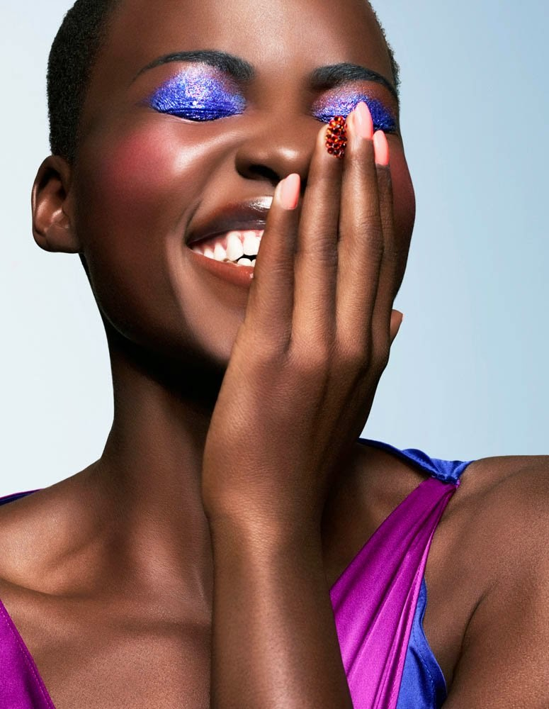 Lupita Nyong'o smiling with eyes closed and hand over the left half of her face