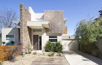 fachada de casa moderna pequeña con gran muro de piedra