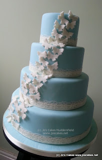 4 tier blue wedding cake with butterflies and lace