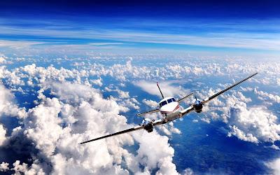 Avioneta en pleno vuelo con cielo despejado y algunas nubes