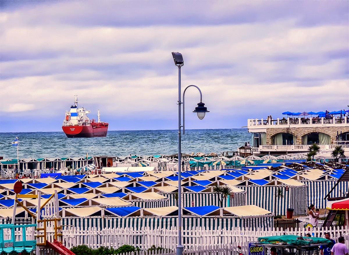 Un barco en el mar y  carpas en playa.