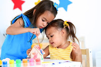 two girls paint together NAMC montessori schools ministry regulations mixed age groups