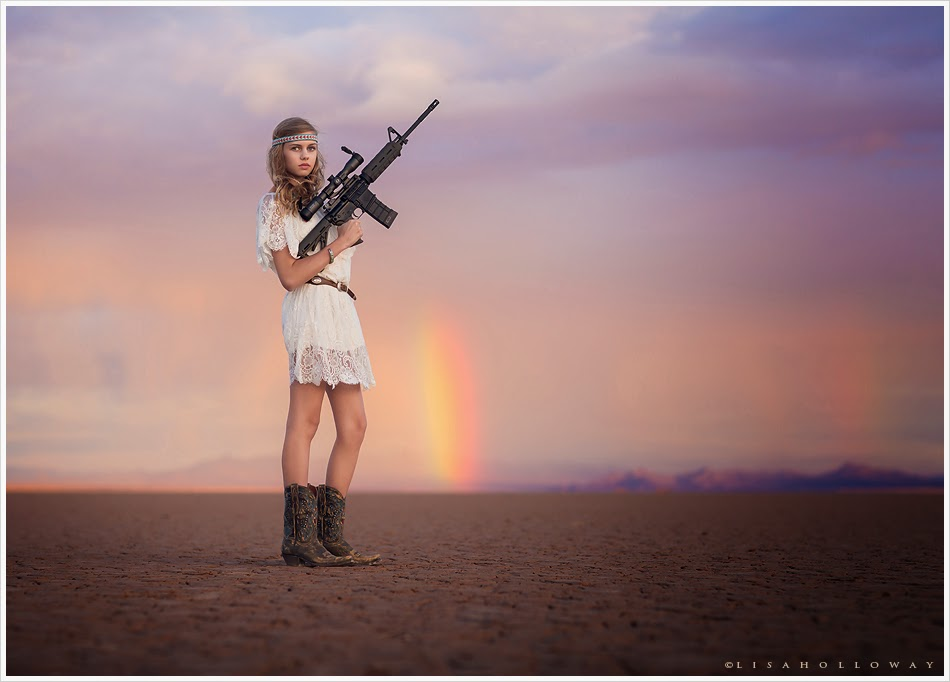 photo de Lisa Holloway représentant une jeune femme en courte robe blanche tenant un fusil d'assaut dans un désert