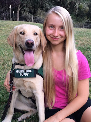 Hailey (wearing a pink t-shirt) poses next to her yellow Lab guide dog puppy (wearing the GDB green puppy coat).