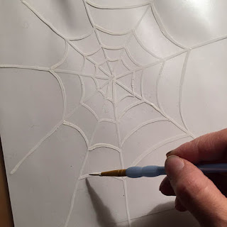 Painting a white spider web on the sticky side of the contact paper