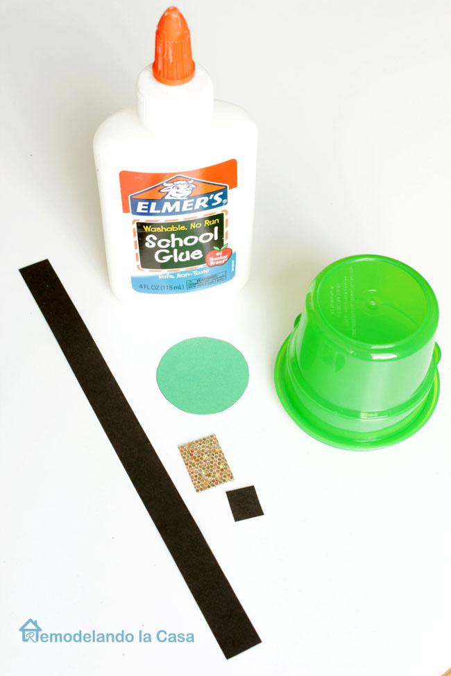 paper, glue and green plastic snack container are the materials used for hats