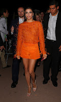 Eva Longoria wearing a bright orange outfit
