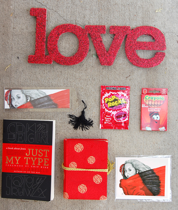 the word love chip board with red glitter, pop rocks candy, crayola red hot crayon pack, just my type book, red journal, red girl 1 bookmark and notecard from The True Colors Collection by Noami Foster