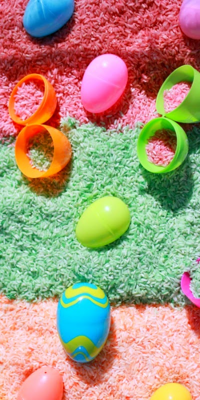 Easter sensory bin with colored and scented rice.  The eggs are full of surprises sure to delight little ones!