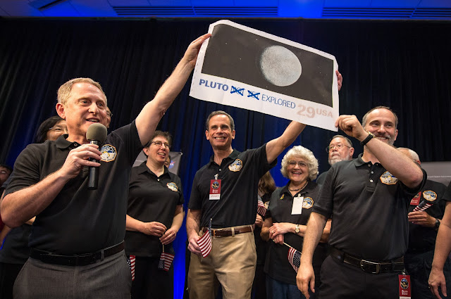 New Horizons Principal Investigator Alan Stern of Southwest Research Institute (SwRI), Boulder, CO., left, Johns Hopkins University Applied Physics Laboratory (APL) Director Ralph Semmel, center, and New Horizons Co-Investigator Will Grundy Lowell Observatory hold a print of an U.S. stamp with their suggested update since the New Horizons spacecraft has explored Pluto, Tuesday, July 14, 2015 at the Johns Hopkins University Applied Physics Laboratory (APL) in Laurel, Maryland. Photo Credit: (NASA/Bill Ingalls)