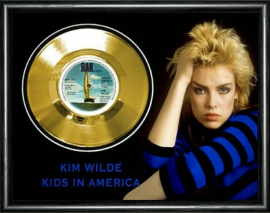 Kim WIlde in a blue and black stripy top