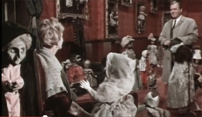 Inspector Holloway and the widow Von Sturm in a room full of dolls