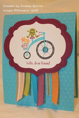 "Turquoise card with orange, purple, green and turquoise ribbon. Colorful focal image of a frog riding a tricycle with the sentiment ""hello, dear friend."""