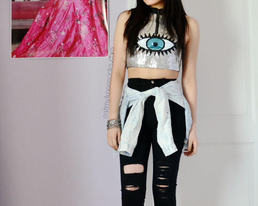 For less than $30, you can get the sequined eye pattern crop top and the black ripped high-waisted skinny jeans shown here, from SheInside.