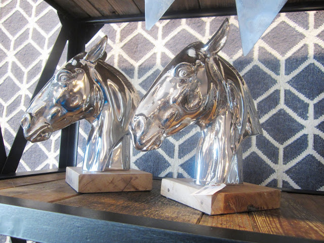 Silver horse head statues mounted on wood blocks