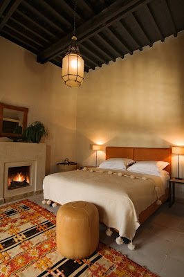 dormitorio con detalles color naranja alfombra cabecera ampara chimenea cuadro