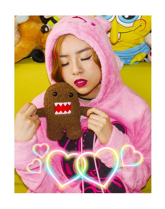 Girl wearing pink gloomy bear hoodie posing with Domo