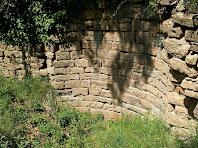 Restes del mur del pou de descàrrega de la bassa del Molí d'Altimires