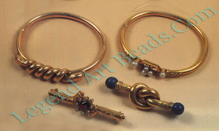 Gold tube replica style jewelry (c. 1870). Top, two bangles, one with coiled serpents, the other with freshwater pearls. Below them, two bar brooches, one set with an almandine garnet, the other a simple overhand knot with lapis-lazuli bead terminals.