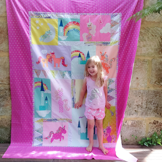Isla standing in front of her new Liberty print Unicornia Quilt, pattern by claire turpin designs