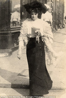 Edwardian Street Fashion depicts a woman reading as she walks down the street.