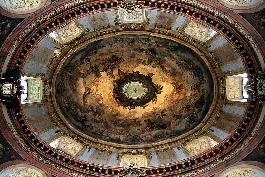 Foto vista de baixo sobre a tecto de uma cúpula em formato oval  com pinturas, preenchido em redor com oito janelas.