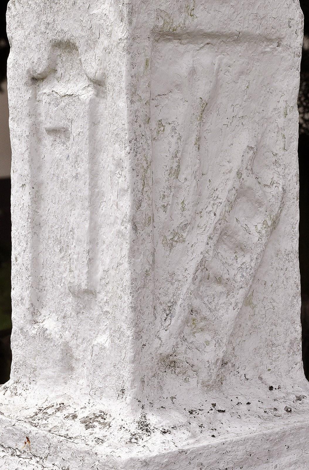 Mokra k. Stąporkowa, Żeliwny krzyż na kamiennym postumencie. Kamienny postument - widok z przodu: od góry widoczny wykuty krzyż łaciński (zwykły) - crux ordinaria, poniżej Arma Christi: drabina, obcęgi (ukryte pod grubą warstwą farby), po lewej stronie kolumny nie rozpoznany symbol. Foto KW.