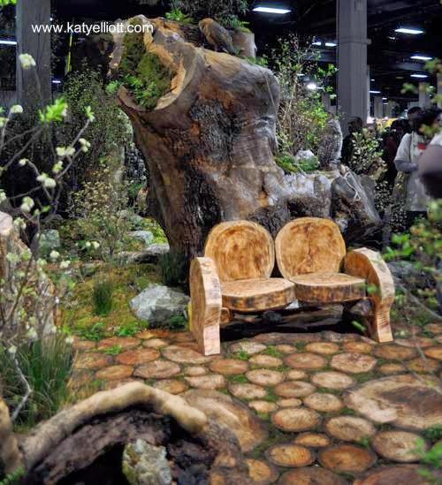 Sector de un jardín con camino de troncos y asiento de discos de madera