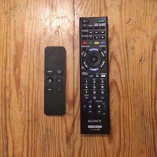 apple tv:n ja sony bravian kaukosäätimet, sonyn on isompi ja monimutkaisempi