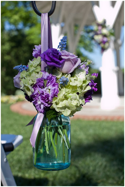 Blue mason jar, green hydrangea, purple stock, purple rose, green hypericum berries, grape hyacinth