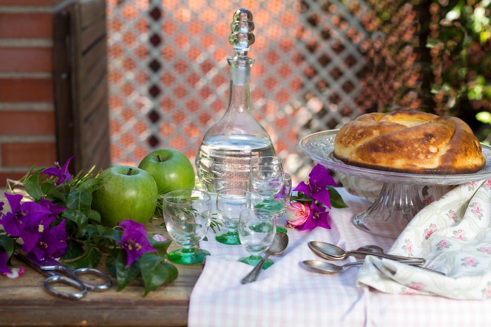 Tarta de requesón en pedestal de cristal con manzanas verdes licorera antigua con flores verdes y púrpura