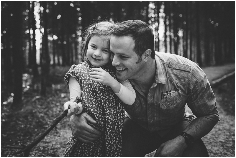 Dad laughing with daughter in the forest