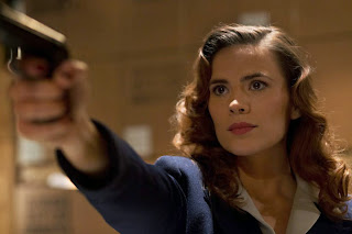 "Screen capture from ABC's ""Agent Carter"" featuring Agent Carter (Hayley Atwell) pointing a gun off stage-right"