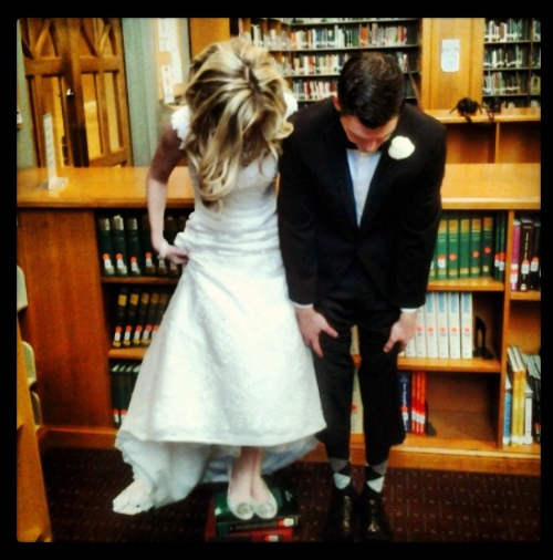 This fun wedding couple picture in a library is whimsical.