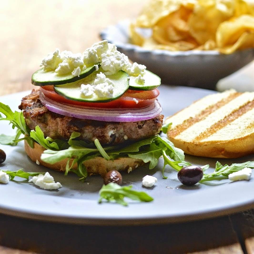 This grilled Greek turkey burger is packed with feta, olives and fresh vegetables and topped with a tangy vinaigrette. Perfect for your summer BBQ!