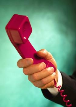 main qui tend un combiné de téléphone
