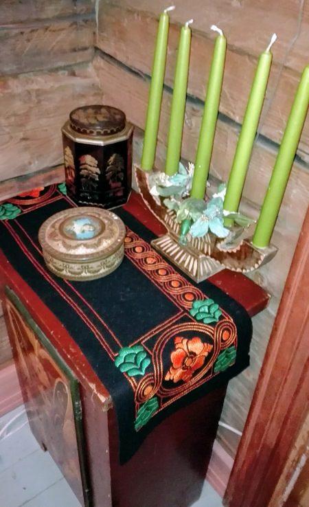 Eteisen pikkukaapin päällä oleva pöytäliina on upea taideteos.