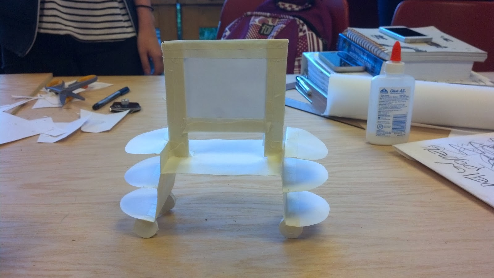 Image shows a small model of the exhibit display made of paper put together with tape. The model sits on a table.