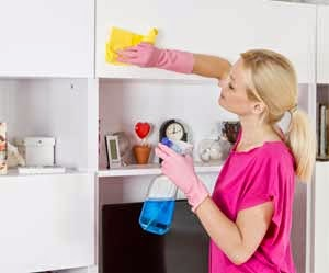 Woman spring cleaning her shelves and cabinets