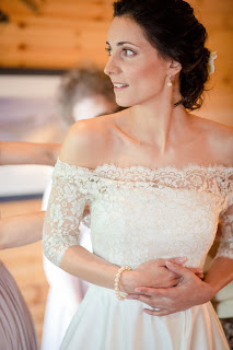 Bride in lace bridal gown with loosely waved upstyle and flower hair accessory