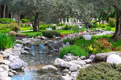 Jardn asitico con ro, plantas y flores de colores