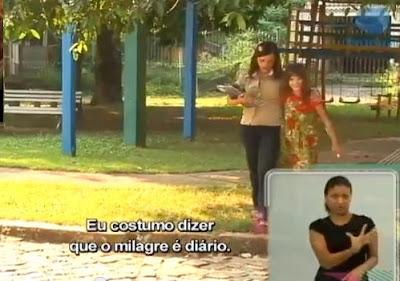 """mãe e filha caminham no parque. Embaixo, a legenda do vídeo diz """"Eu costumo dizer que o milagre é diário"""". Ao lado, em uma janela, uma tradutora de Libras."""