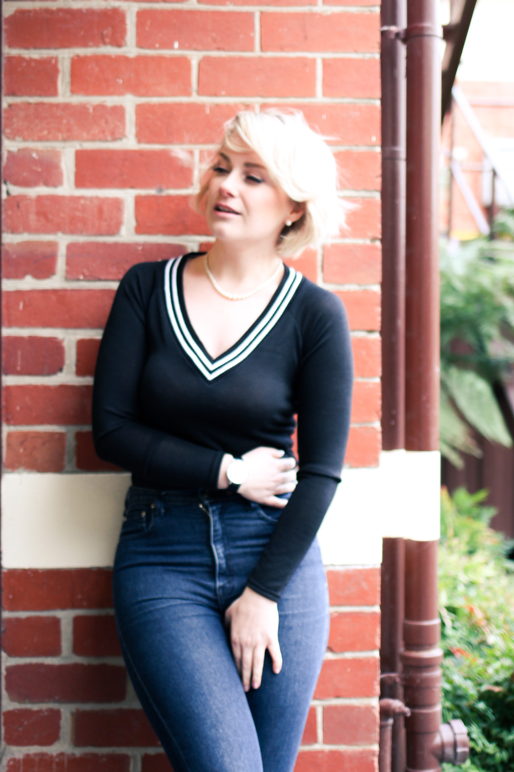 @findingfemme for the BooHoo.com #WeAreUs campaign wearing v-neck sweater and high waisted jeans.