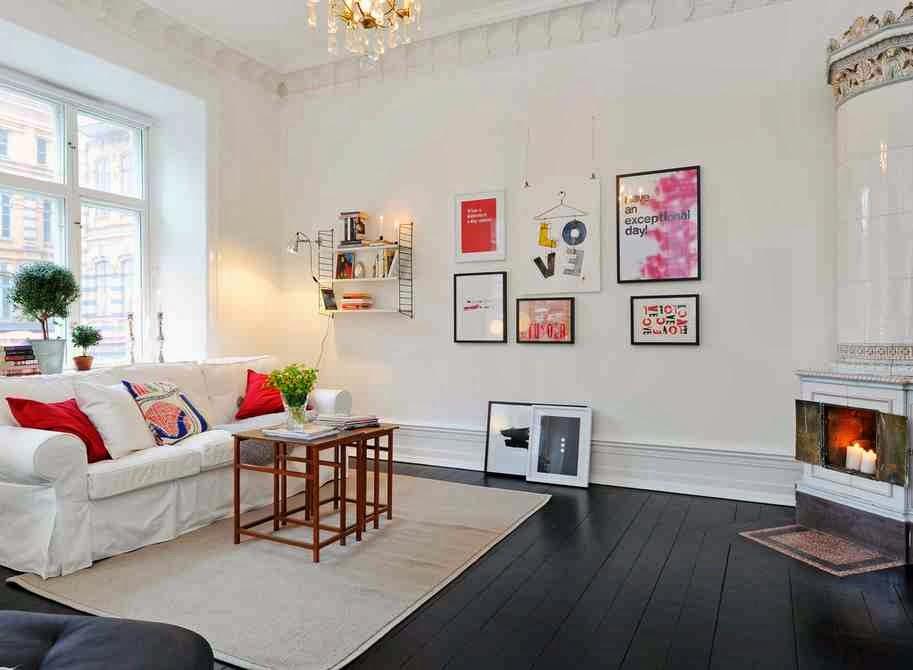 Skandynawskie dekoracje i Czarna podłoga, białe ściany w skandynawskim wnętrzu, kolorowe grafiki w czarnych ramach