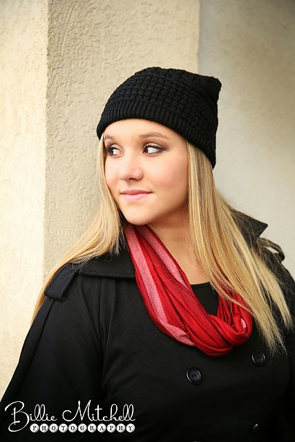 blonde senior girl wearing black slouchy hat, black jacket, and red scarf