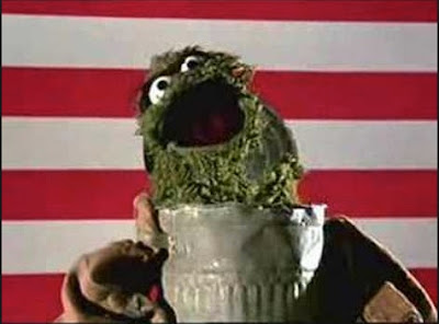 Oscar the grouch singing by his trash can with U.S. flag as backdrop.