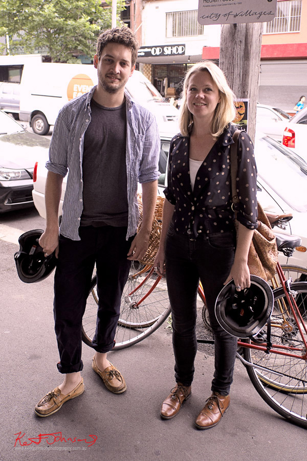 Street Fashion Sydney, Colour co-ordinated couple, Man & Woman cycling Redfern in Leather shoes, Black pants , Tee for him, spotted blouse for her.